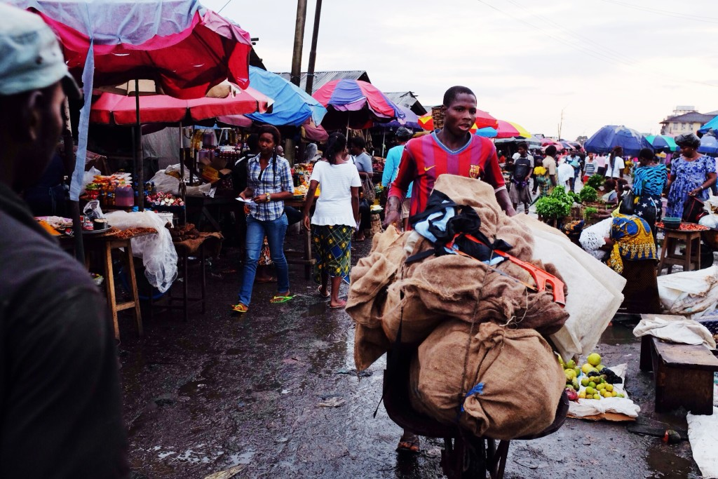 Man pushing a wheel barrow, Creek Road Market, Old Port Harcourt Township