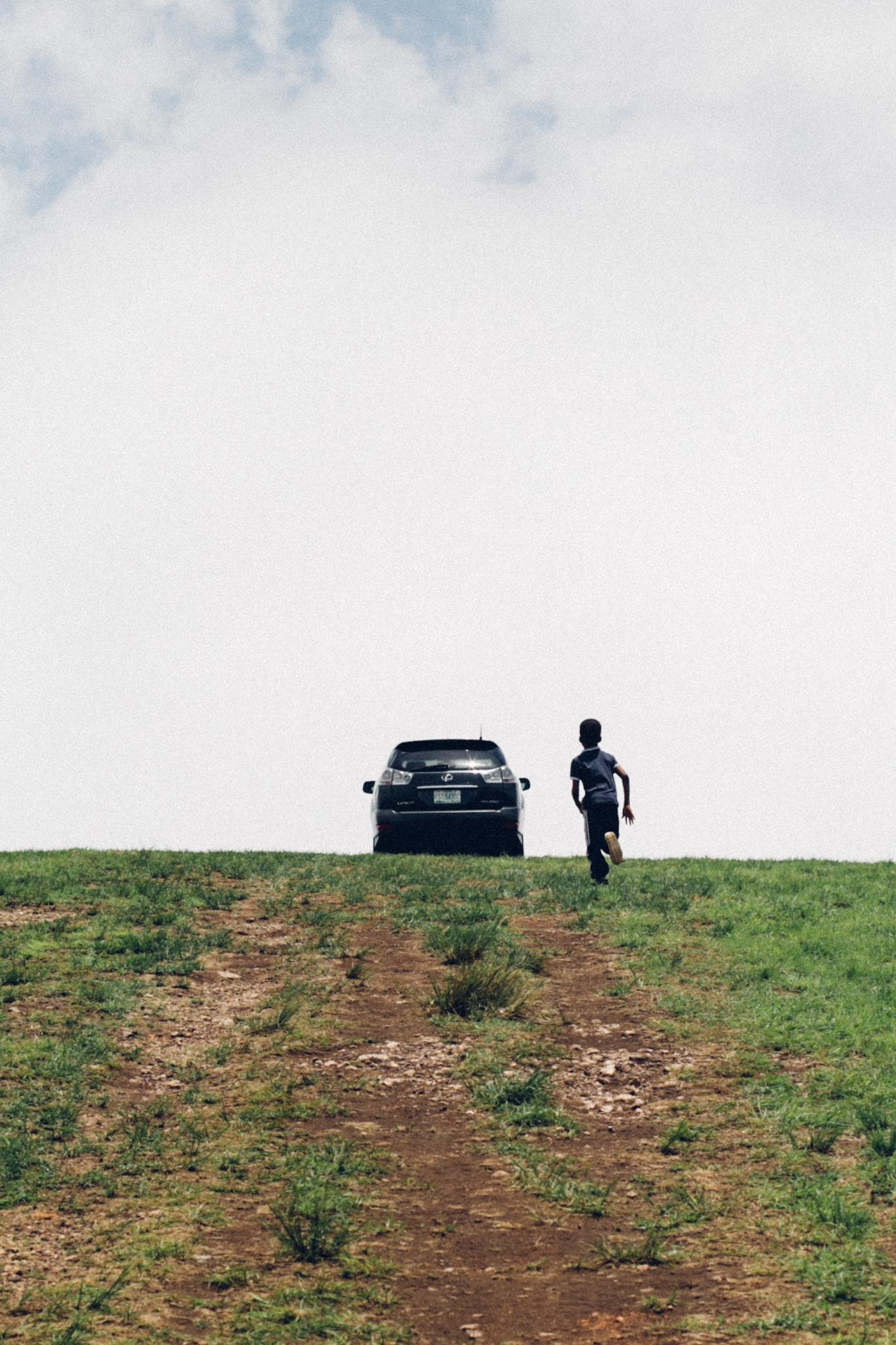 Boy chasing a car on a Hill top, Obudu
