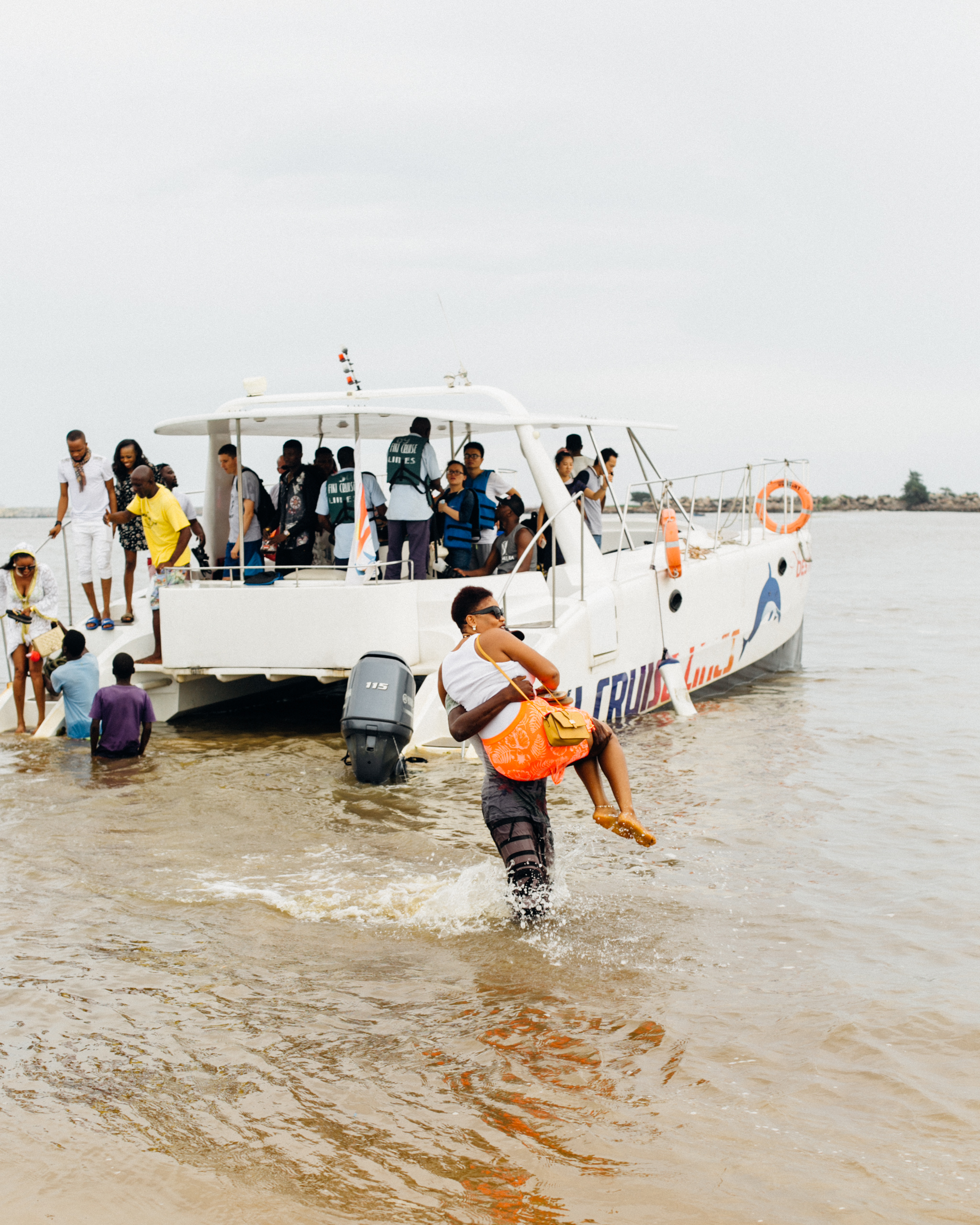 Man carrying a visitor to Tarkwa Bay above water