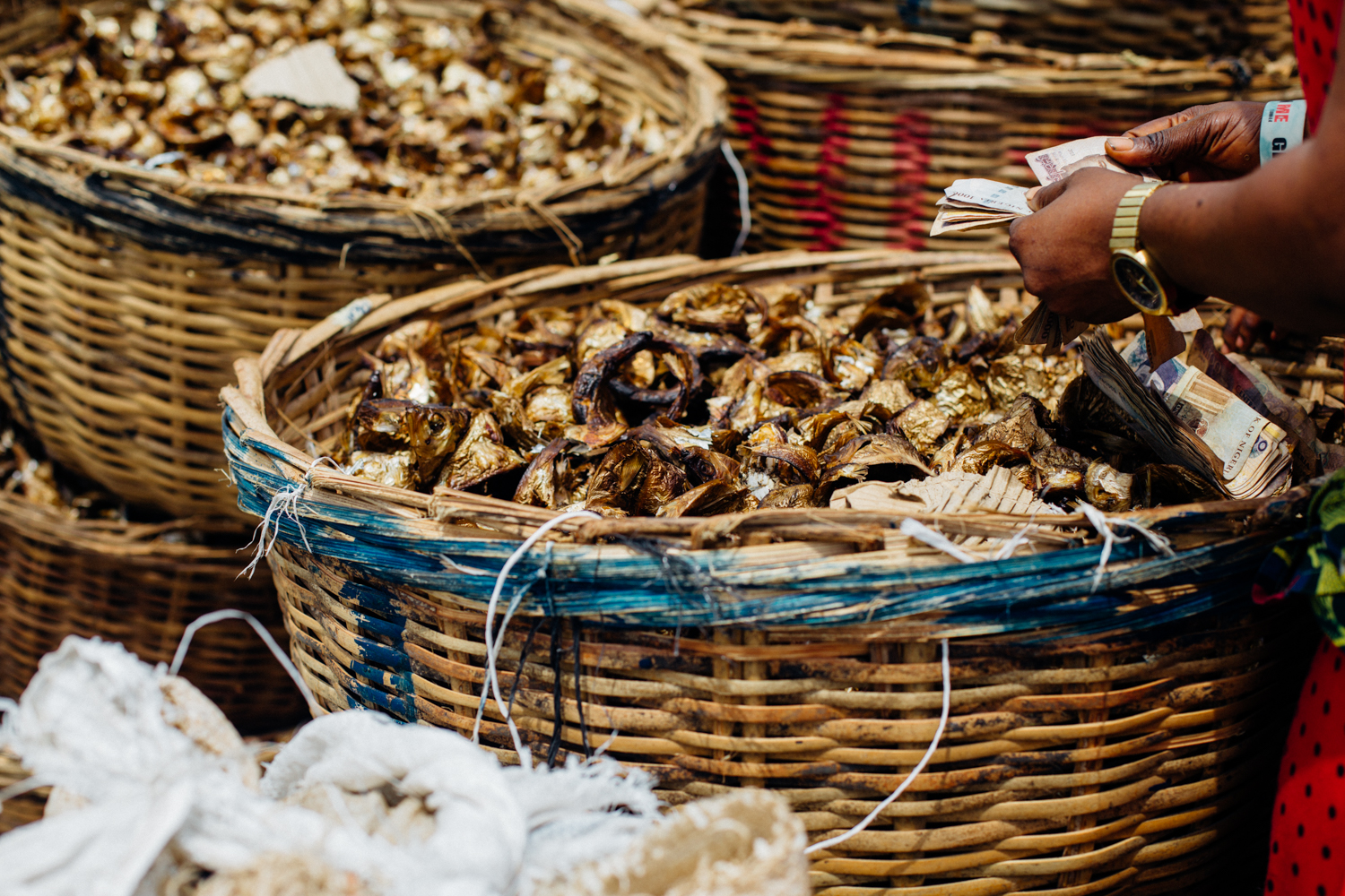Dry fish in baskets and a trader counting money, Koko
