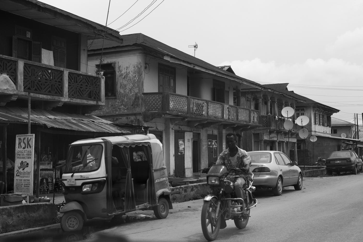 Motorcycle passing by colonial buildings in Sapele