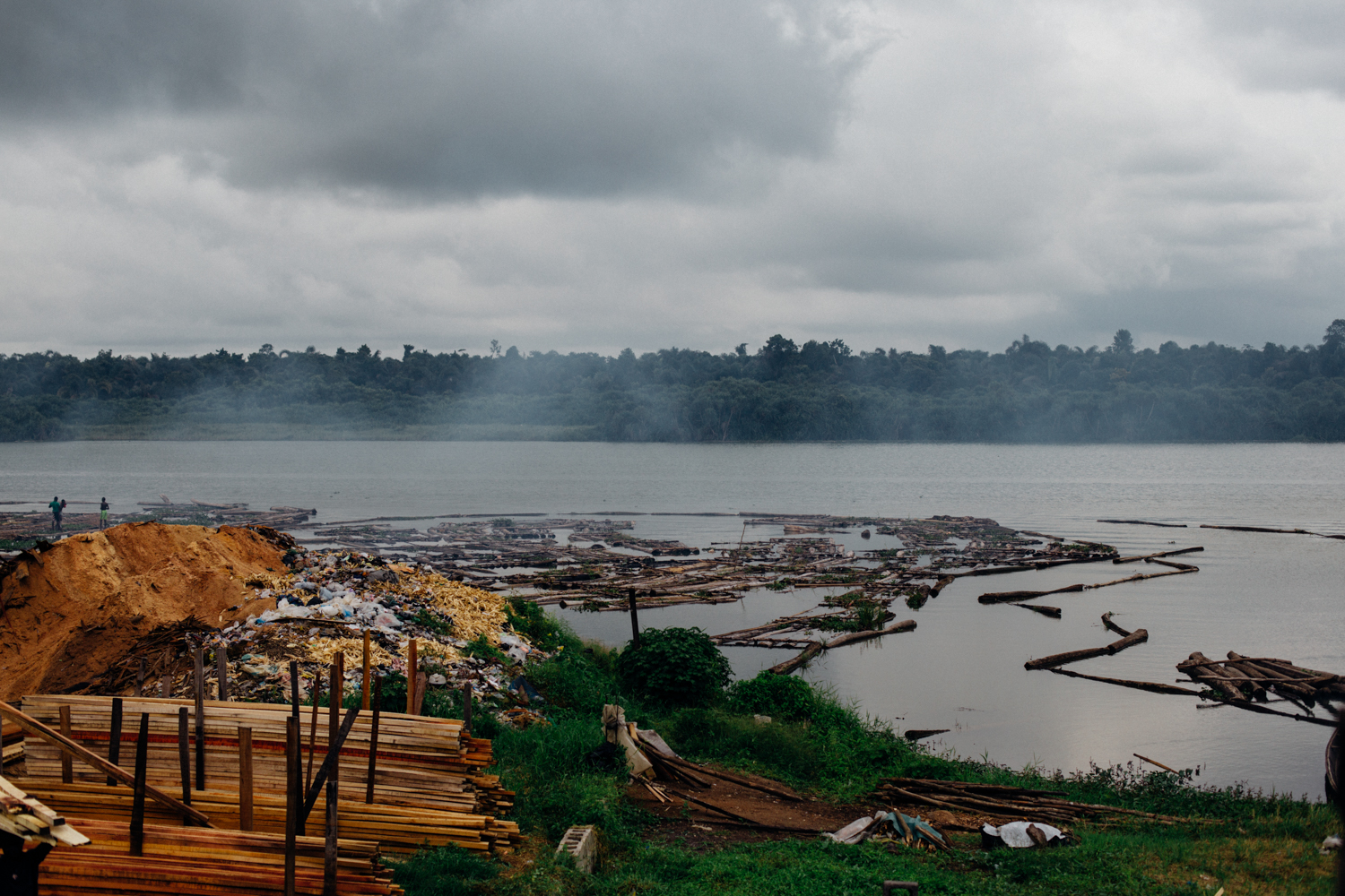 River Ethiope with logs of timber, sawdust and sawed timber in Sapele